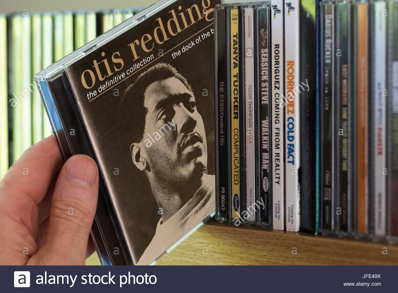 The Dock Of The Bay, Otis Redding Greatest Hits CD being chosen from a shelf of other CD's, Dorset, England - Stock Image