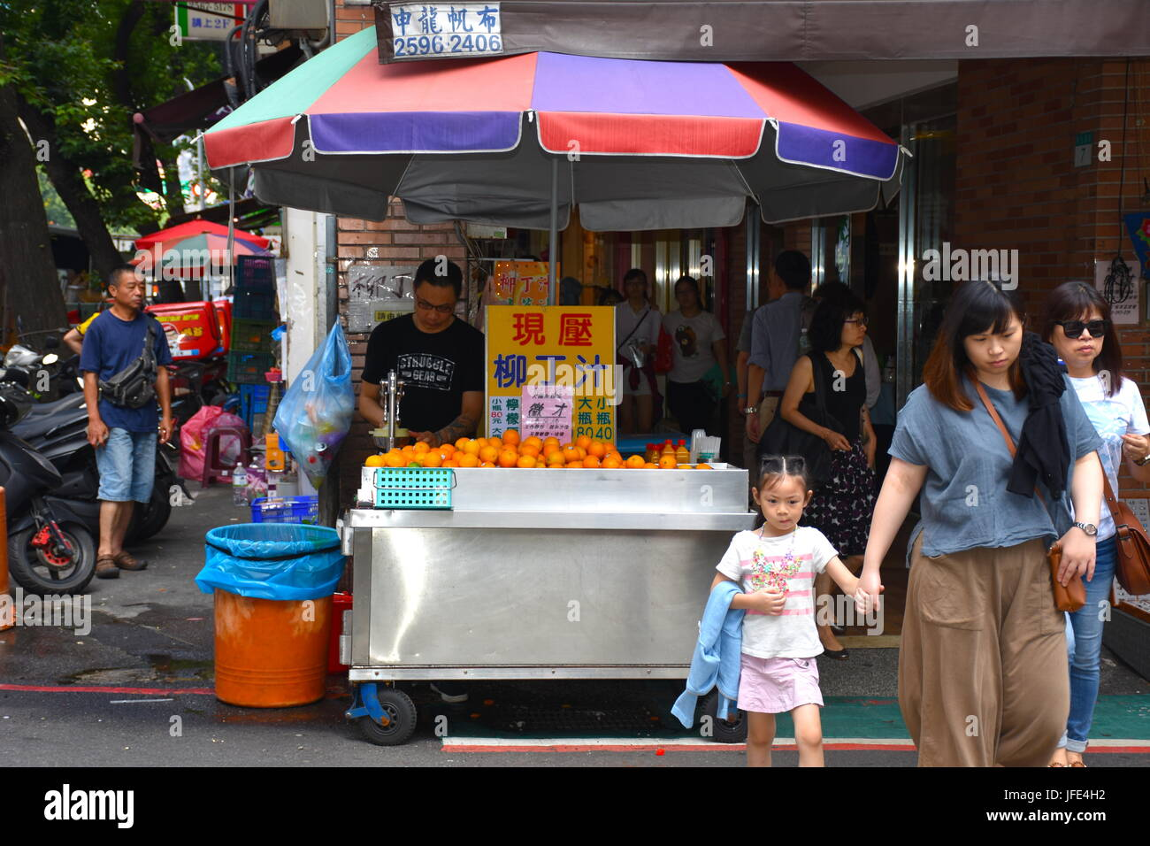 Freshly squeezed orange juice stand just 10 meters from Mackey Hospital in Taipei, taiwan. Super hot day - Stock Image