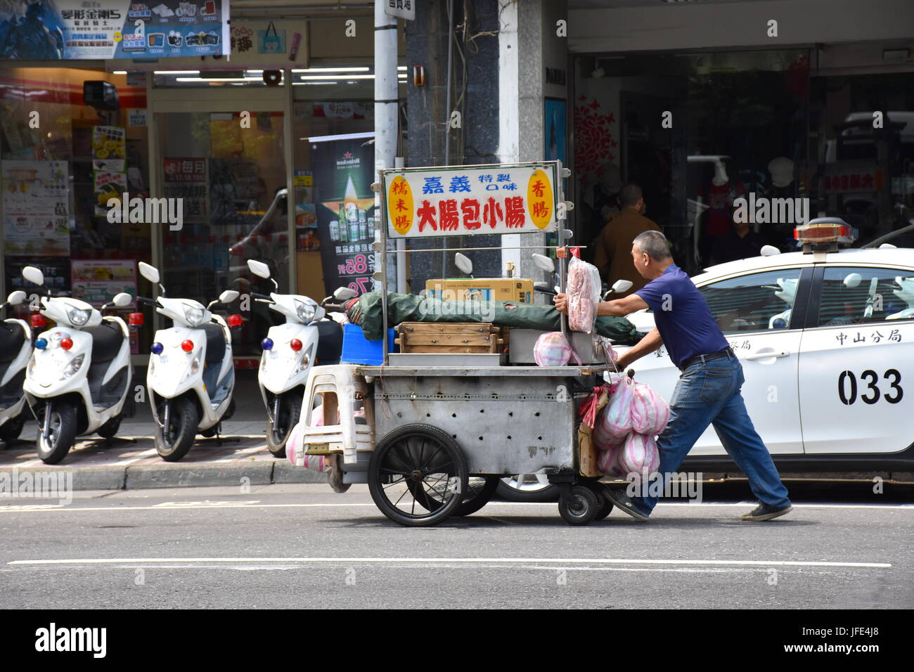 A food stand person pushes his cart past a police station near Mackay Hospital. Taipei, Taiwan. Stock Photo