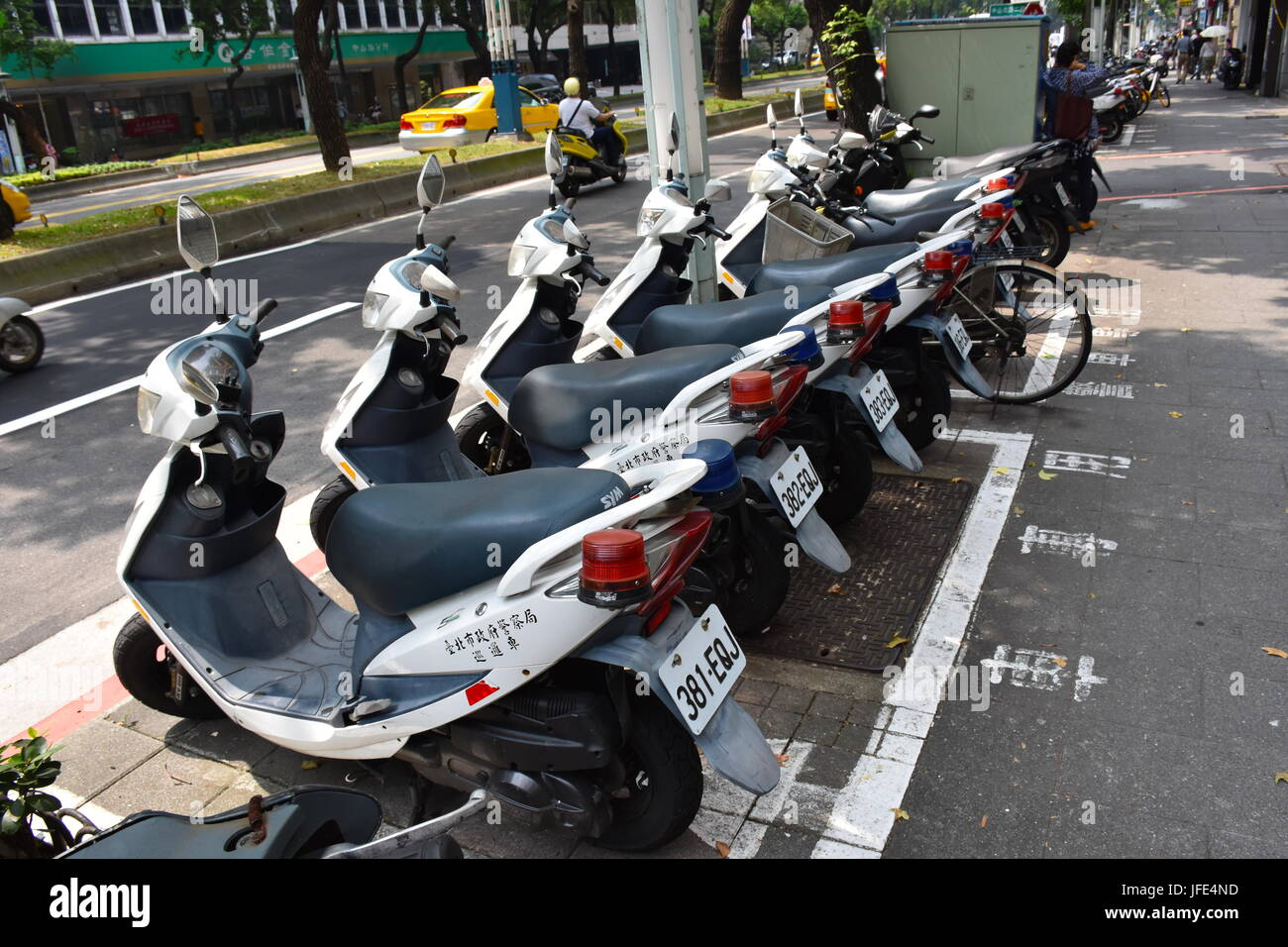 Police officers scooters parked side by side on the sidewalk in Taipei, Taiwan. Its considered normal to see a scooter - Stock Image