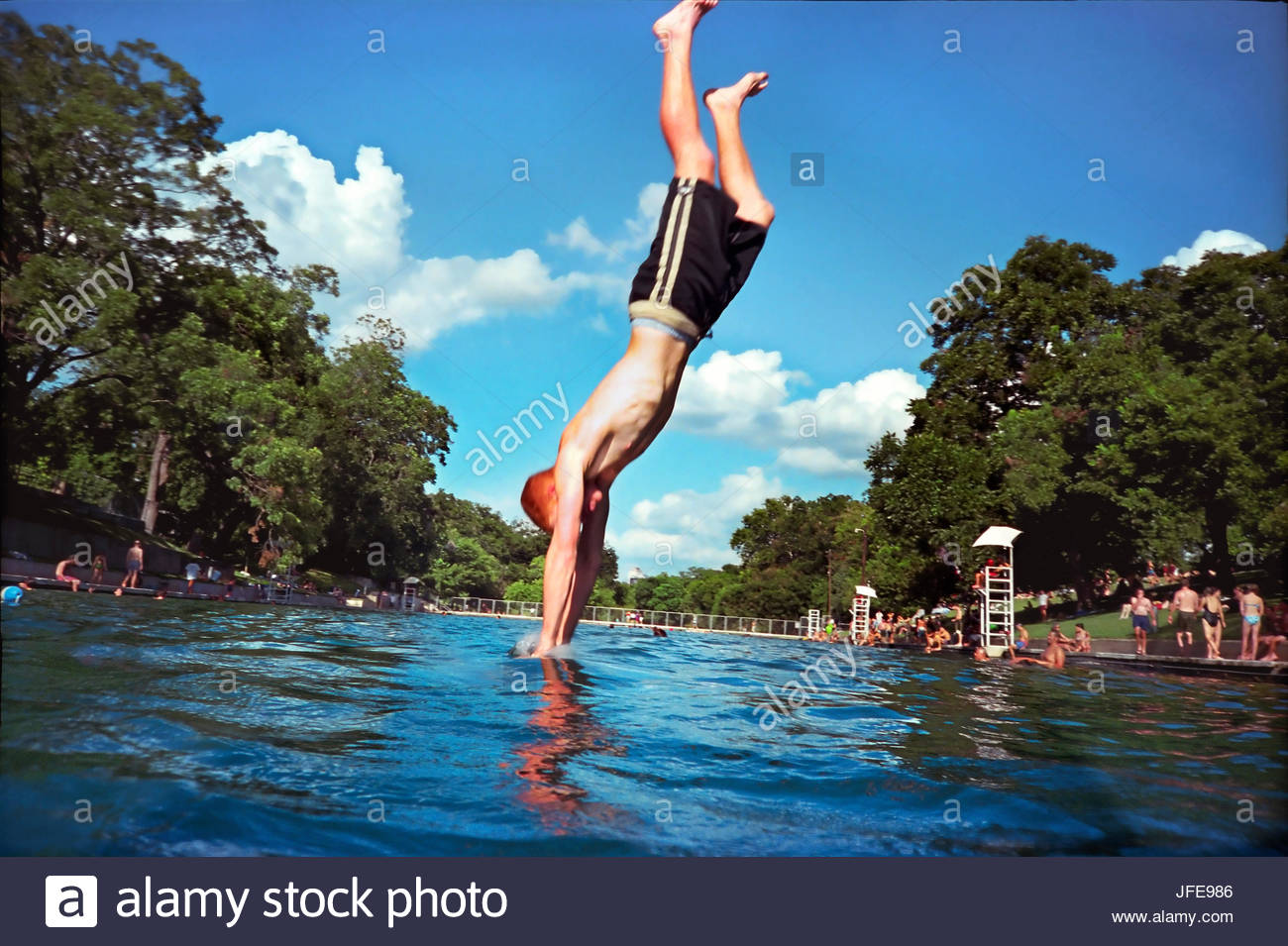 A boy dives into Barton Springs' natural swimming pool. - Stock Image