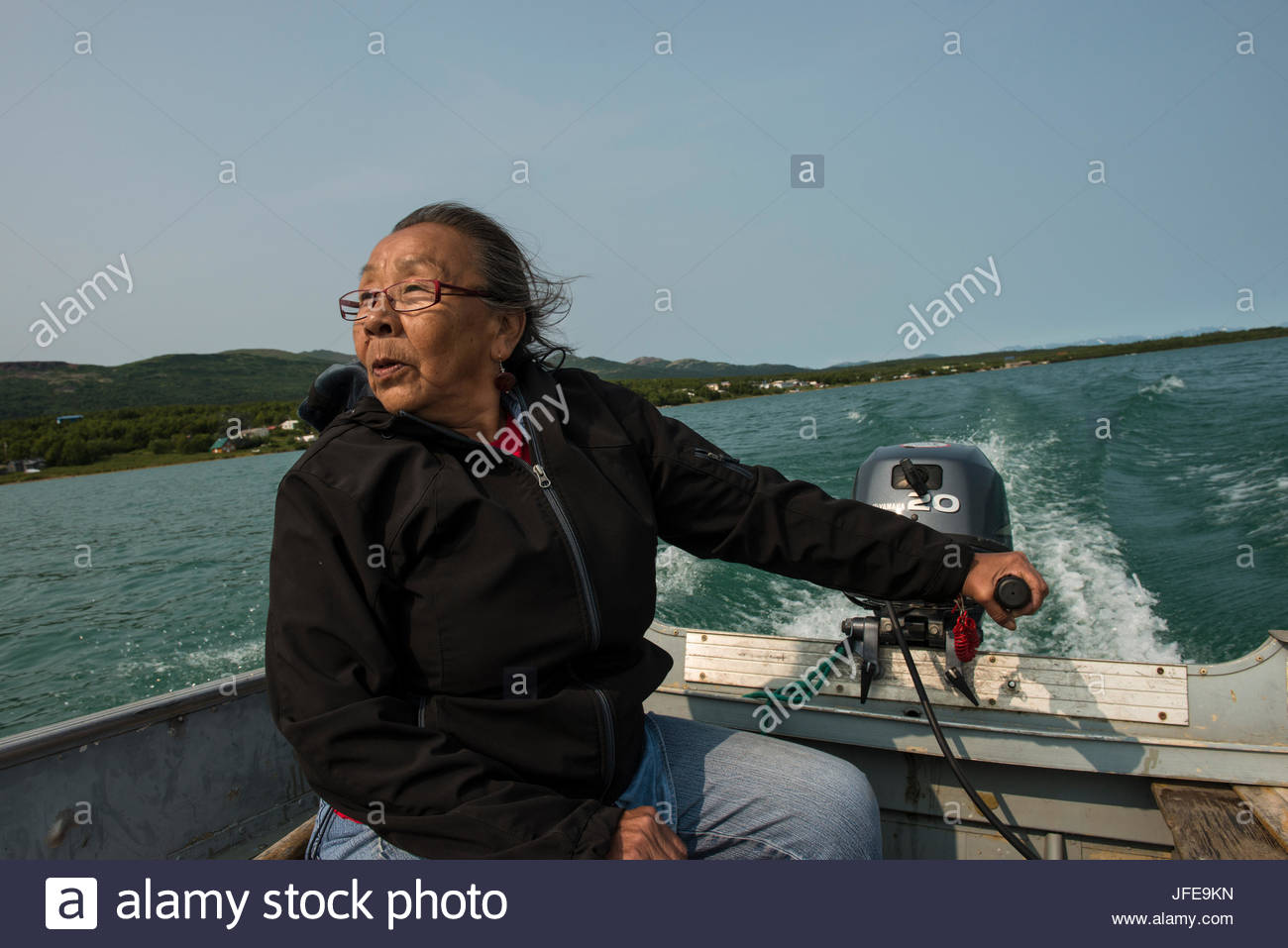 A Dena'ina woman motors down the Newhalen River to her fish camp. - Stock Image