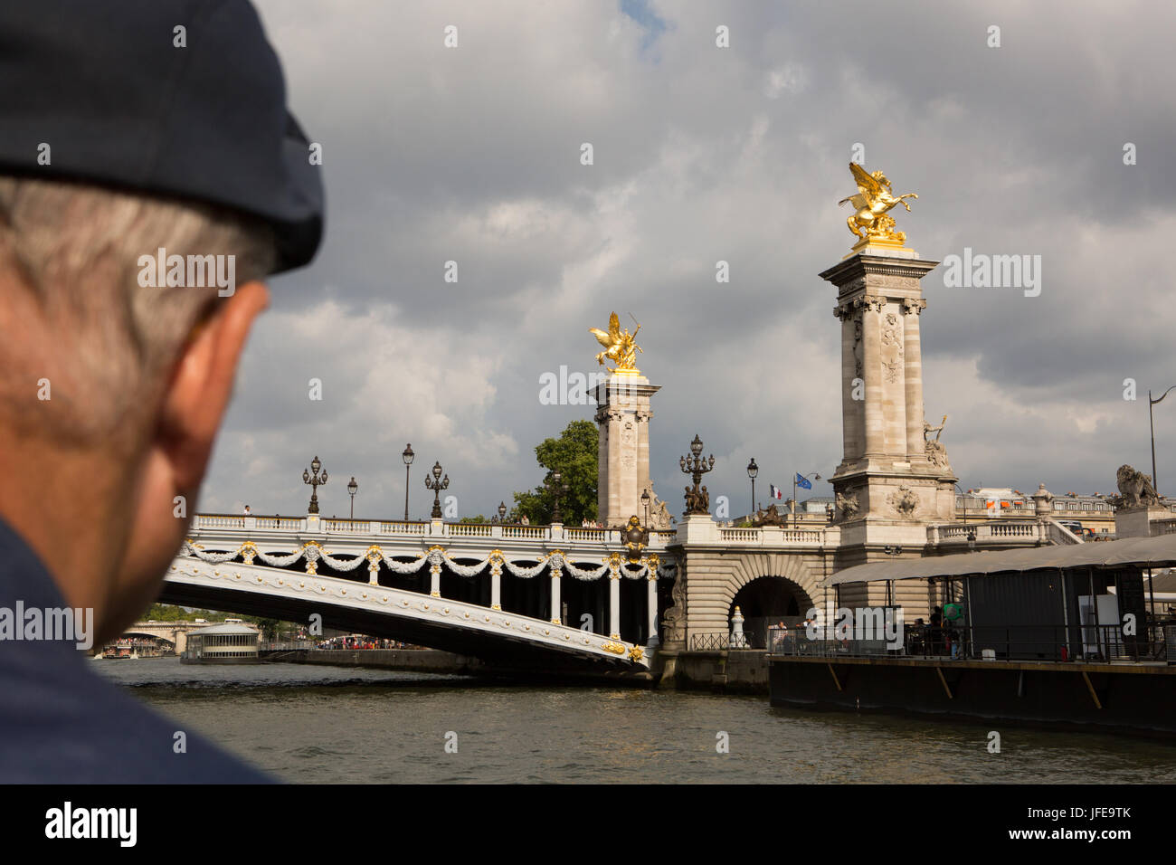A man views the Pont de Alexandre III from a boat cruising on the Seine River. - Stock Image