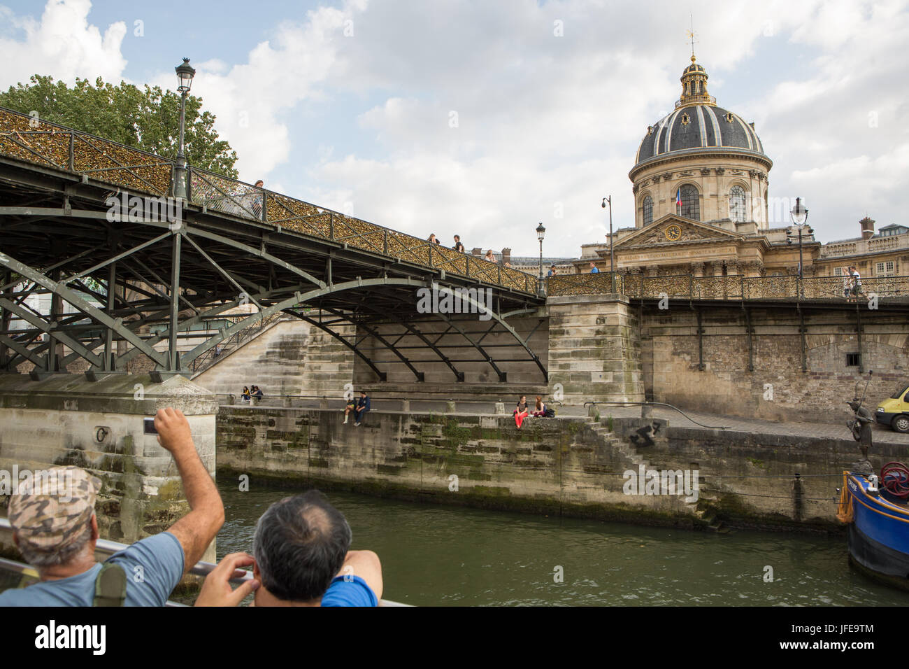 Tourists view the French Institute and the Pont des Arts, or Love Lock Bridge, from a boat cruising the Seine River. - Stock Image