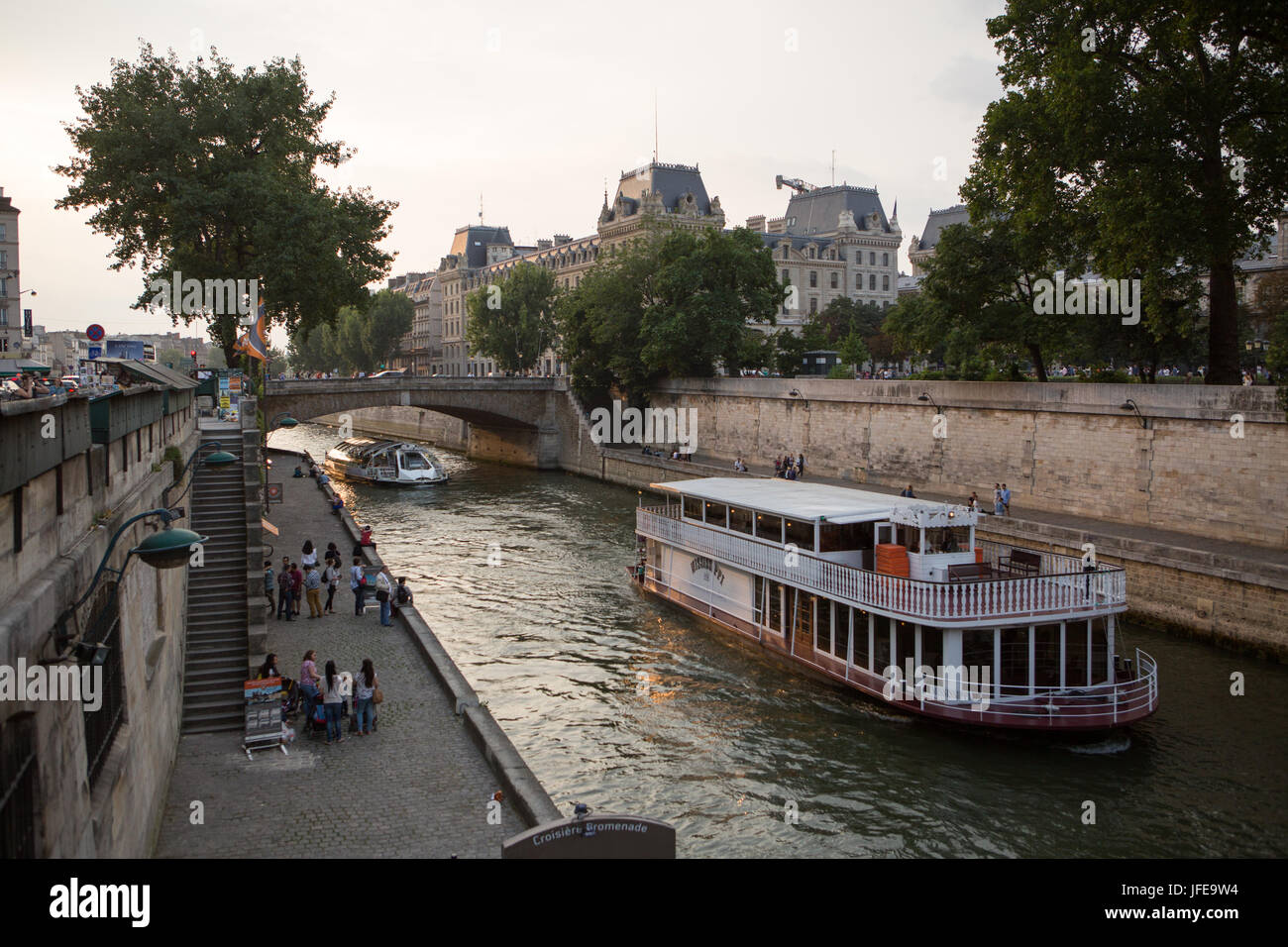 Boats cruise along the Seine River, and Parisians sit along the river banks. - Stock Image