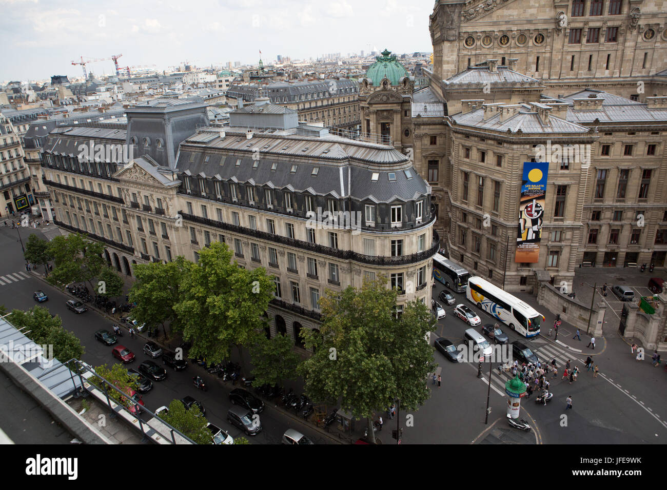 Traffic and pedestrians fill the roads near the Paris Opera House, Garnier Palace. - Stock Image