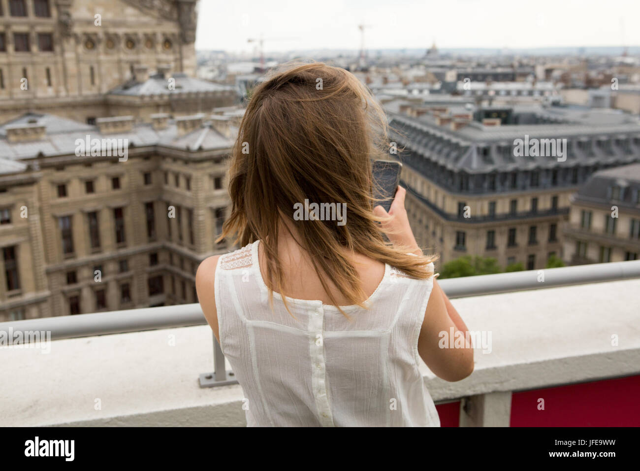 A girl photographs the Paris Opera House, Garnier Palace, and the city landscape. - Stock Image