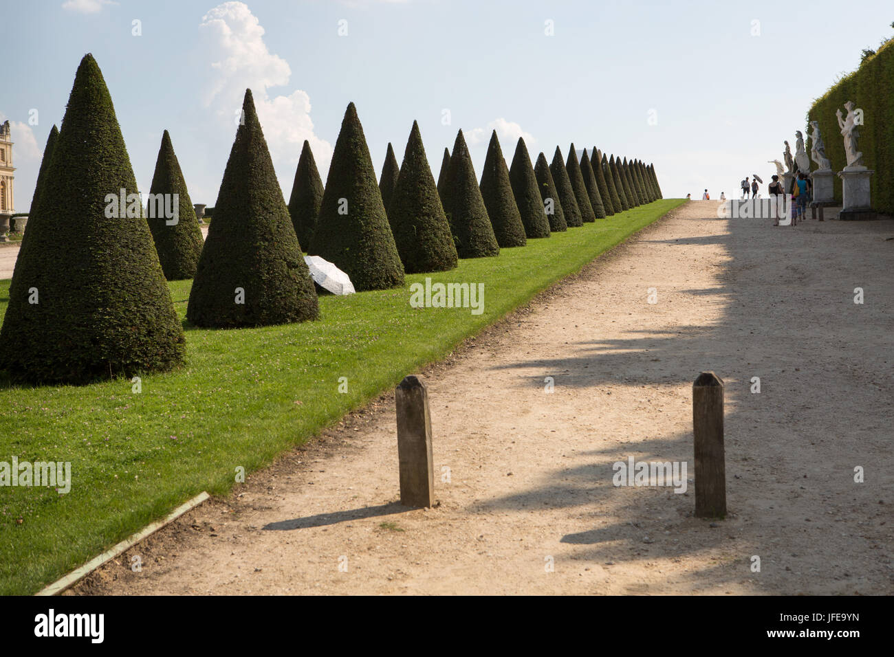 People use umbrellas for shade near groomed trees in the gardens at the Palace of Versailles. - Stock Image