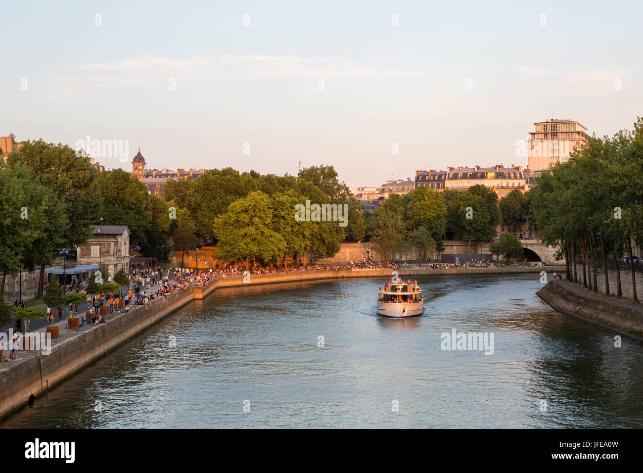 A passenger boat with tourists cruises along the Seine River while Parisians sit along the river banks. - Stock Image