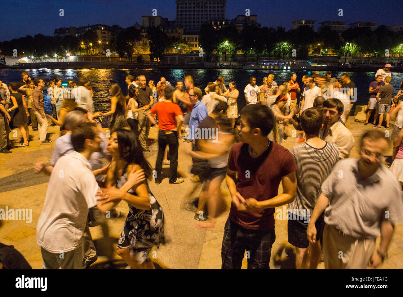 On summer nights Parisians learn and dance the tango near the Seine River. - Stock Image