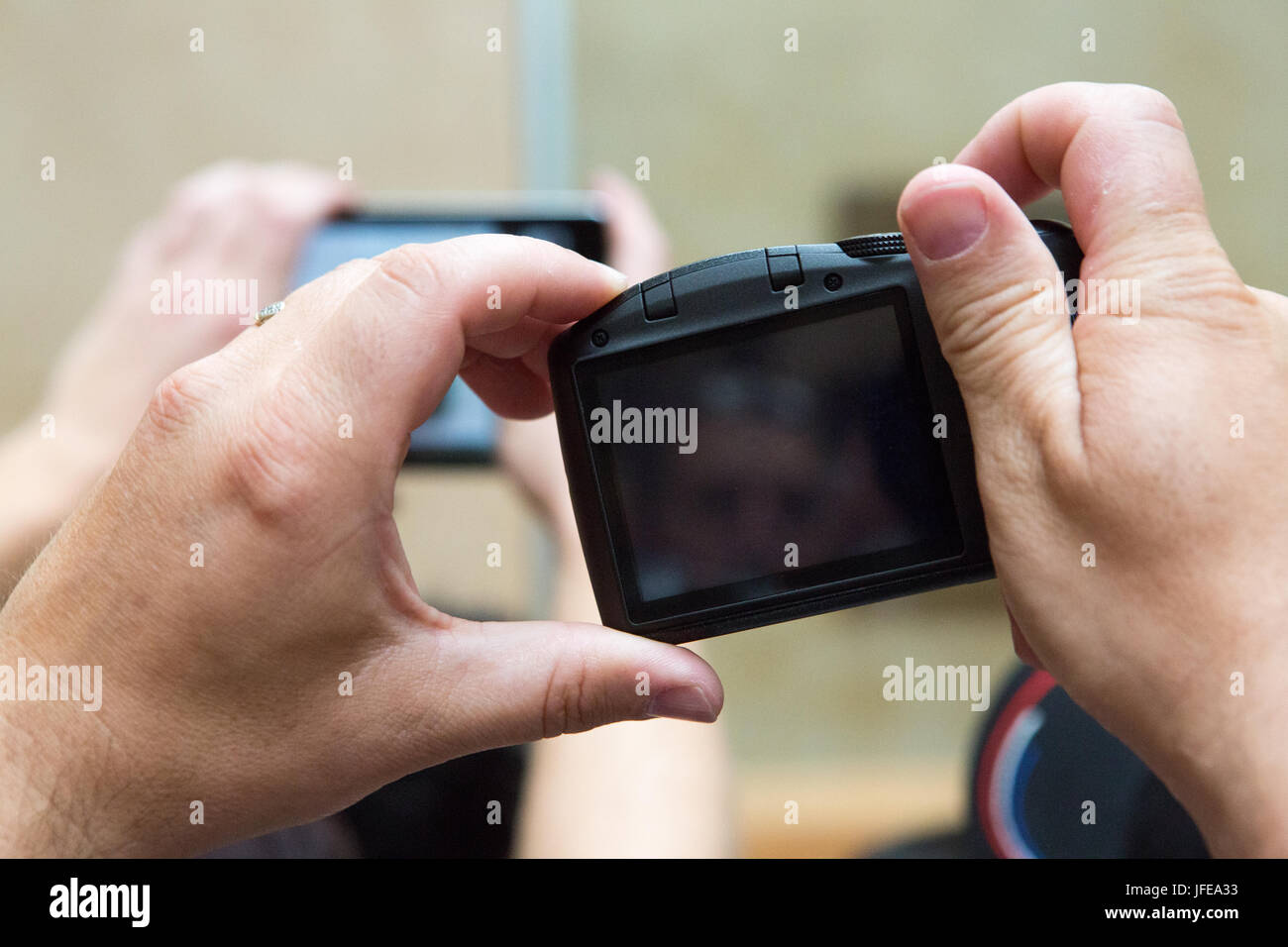 People holding their cameras to take pictures in the Louvre Museum. - Stock Image