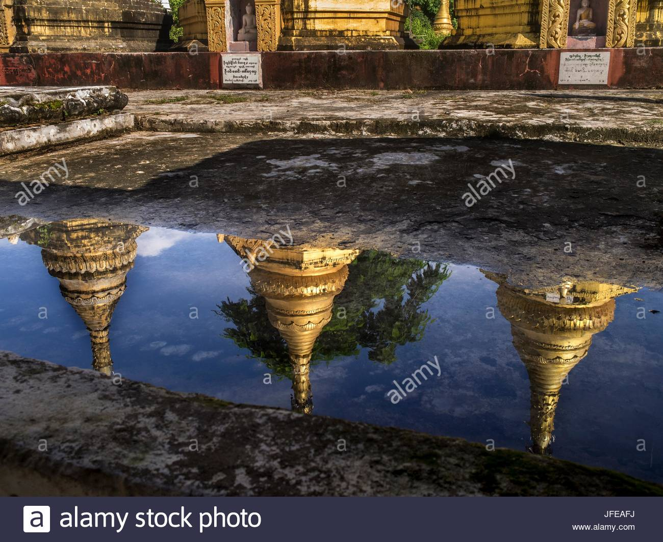 Pagodas are reflected in a puddle of water. - Stock Image