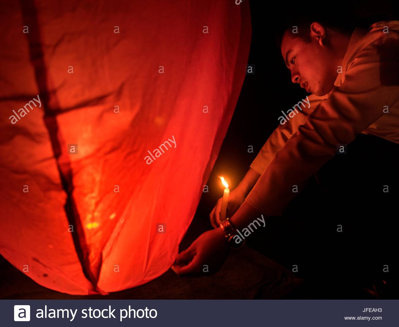 A man lights a candle for a balloon ceremony. - Stock Image