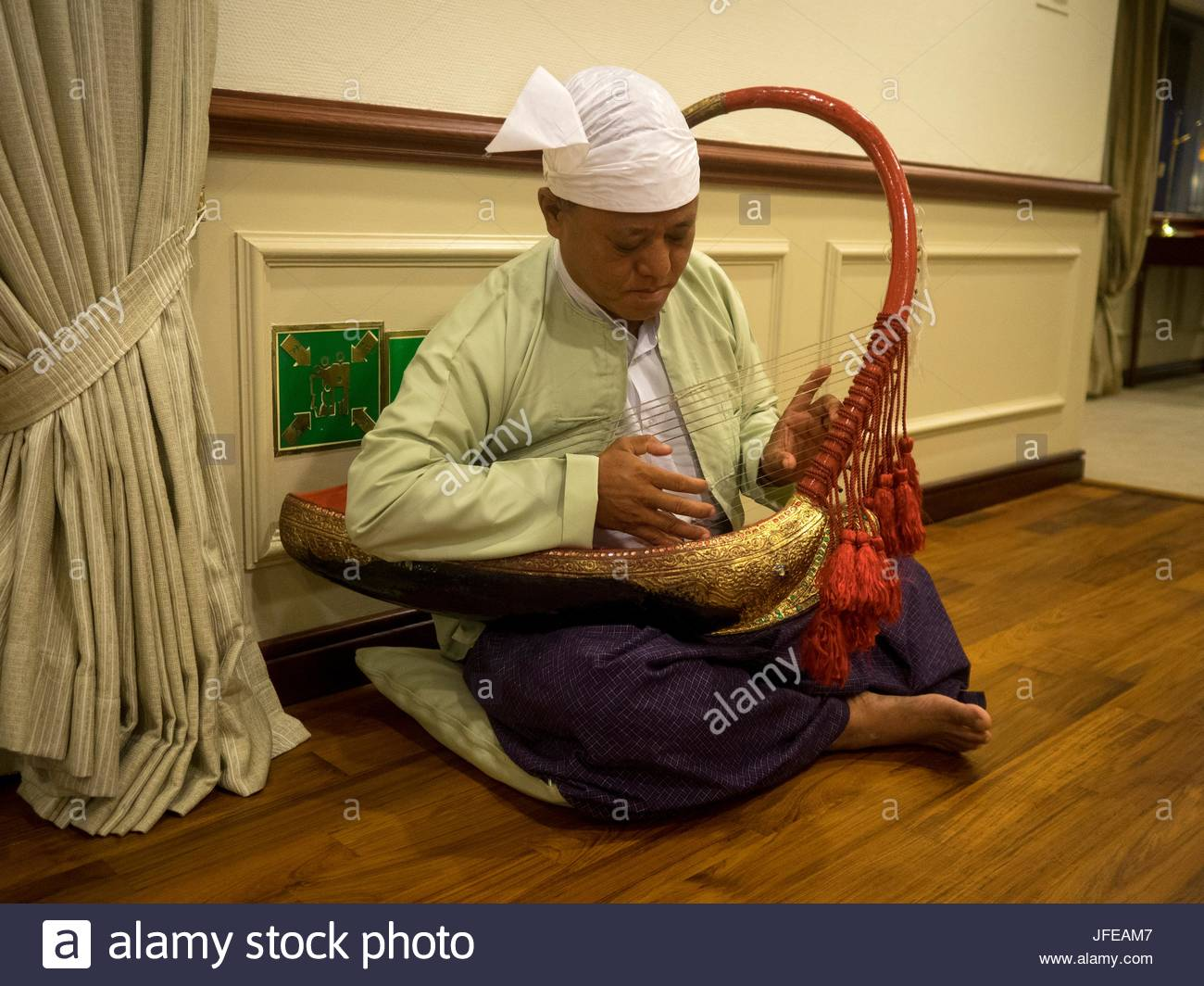 A man plays a traditional musical instrument. - Stock Image