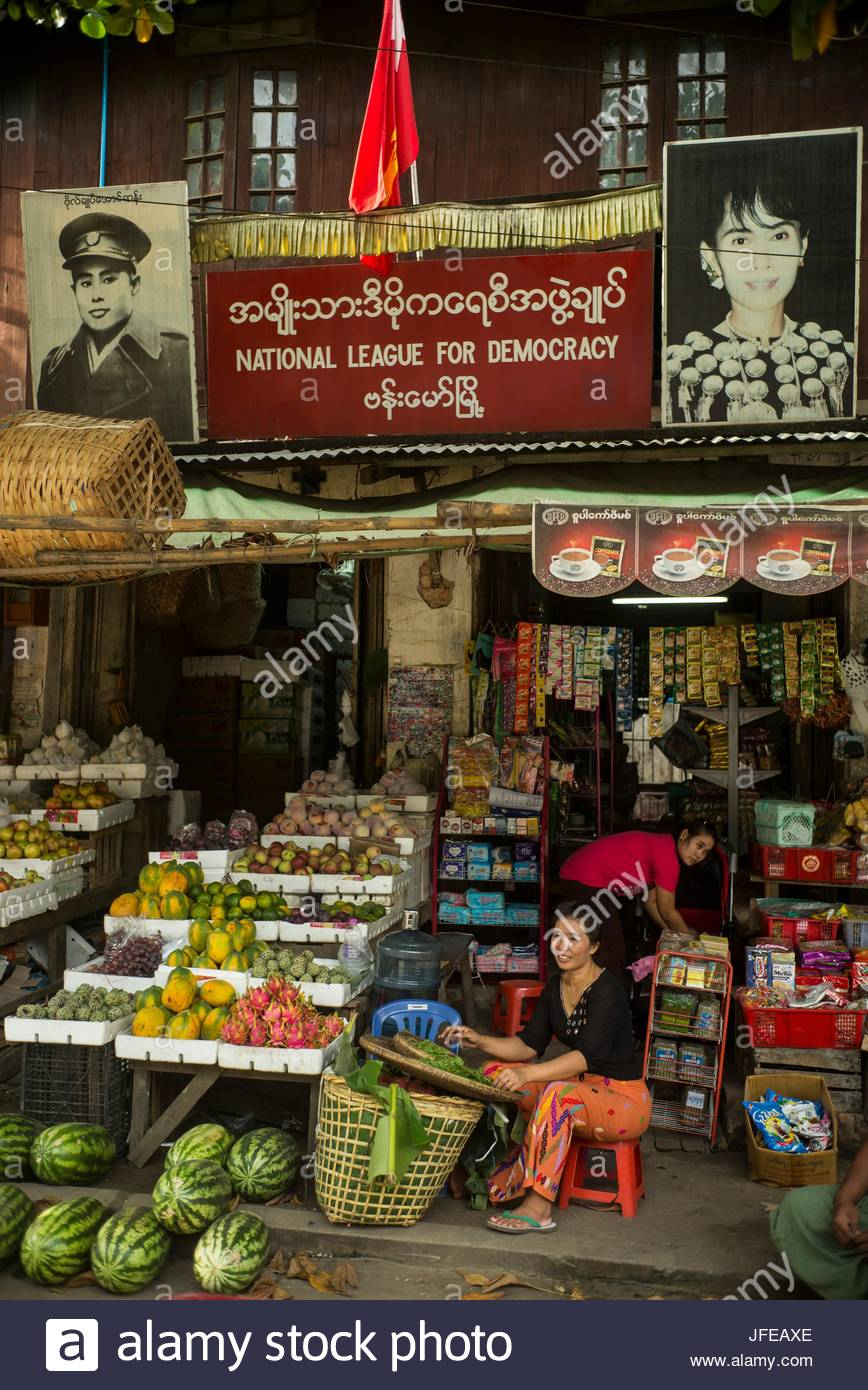 A picture of political leader Aung San Suu Kyi hangs above a market stand. - Stock Image