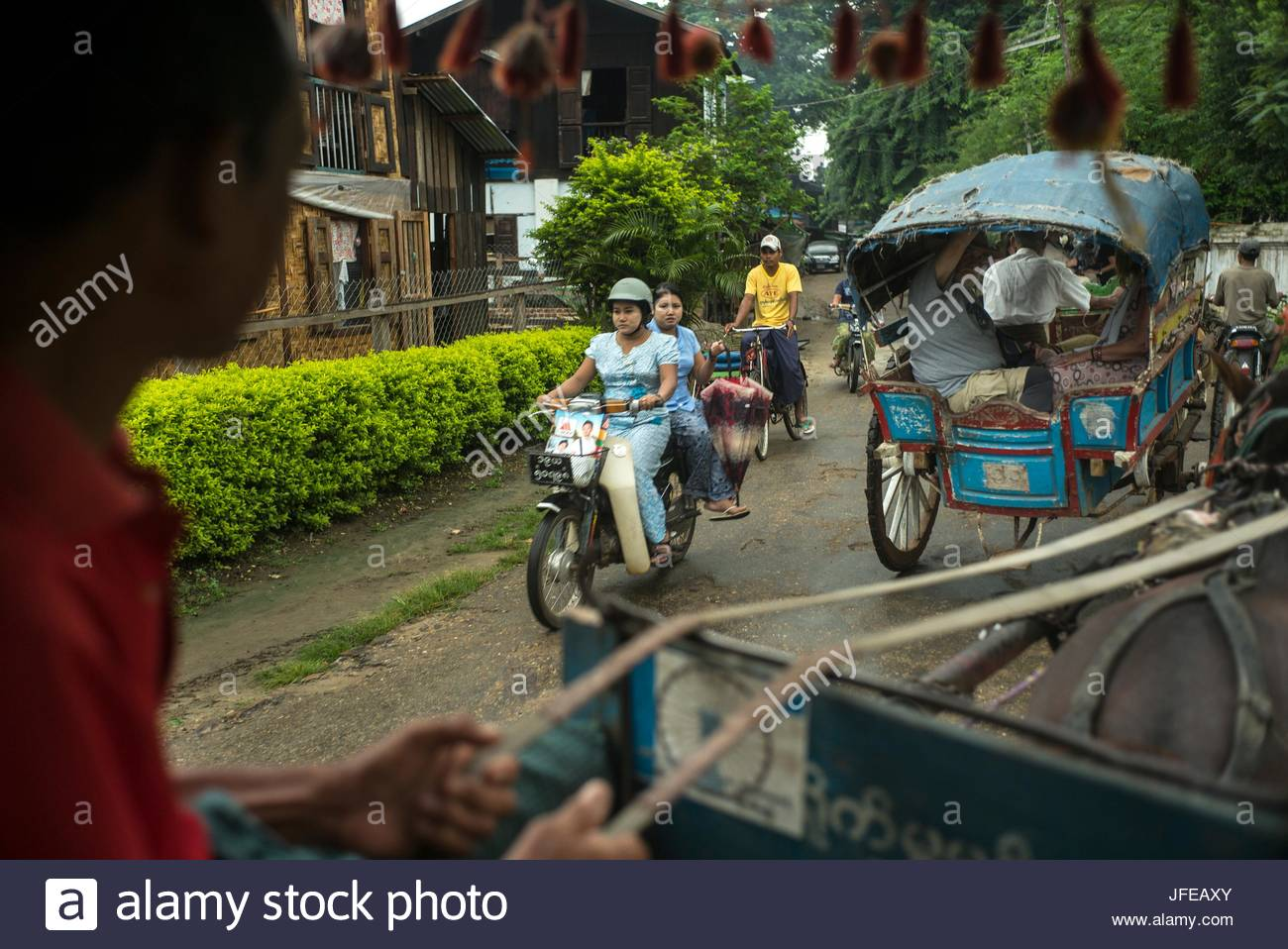 People ride on motorbikes and carriages through Katha, Myanmar. - Stock Image