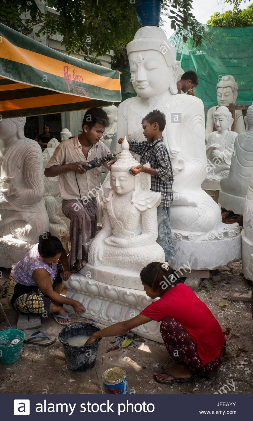 Boys and girls carve Buddha statues out of marble. - Stock Image