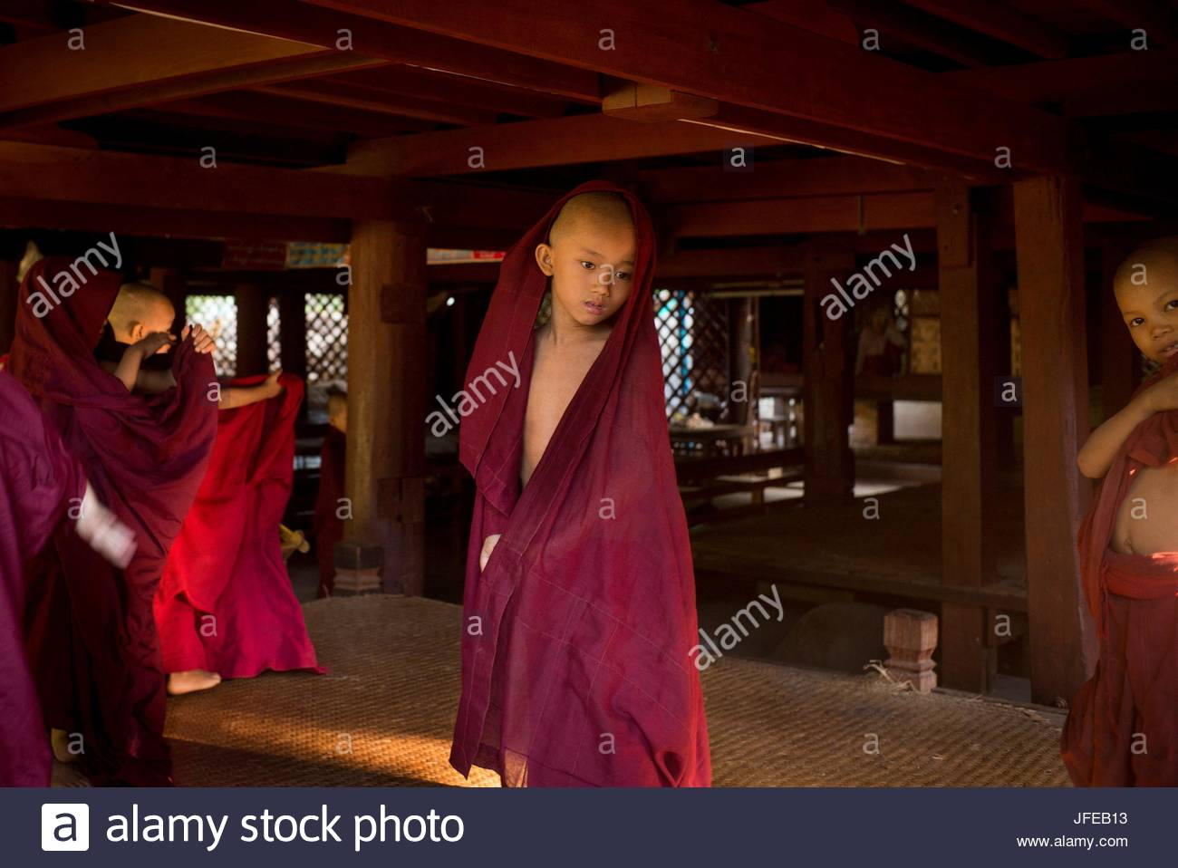 Young monks stand in dark red robes the Shwe Chan Thar Monastery. - Stock Image