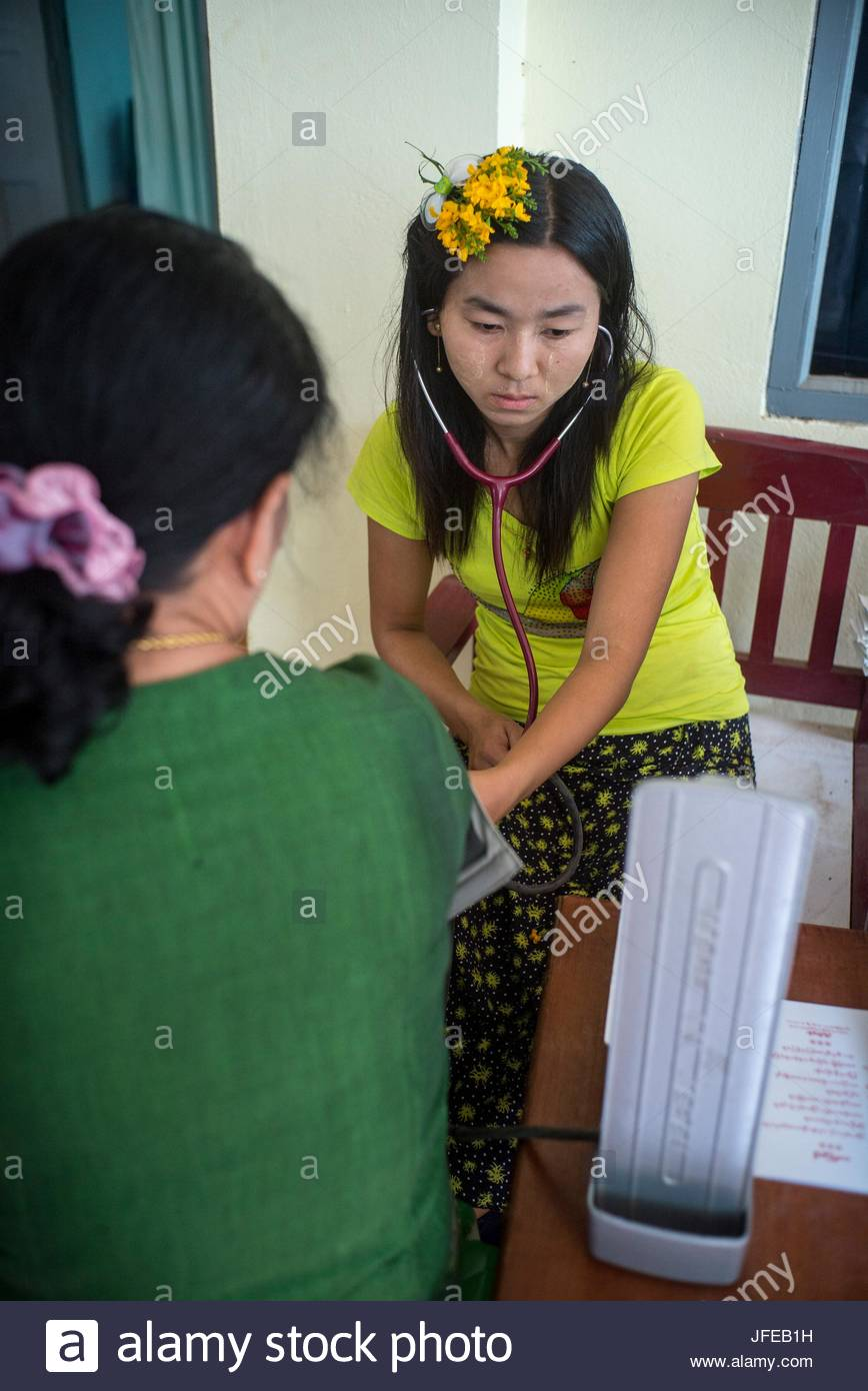 A woman checks a patient's blood pressure at a clinic. - Stock Image