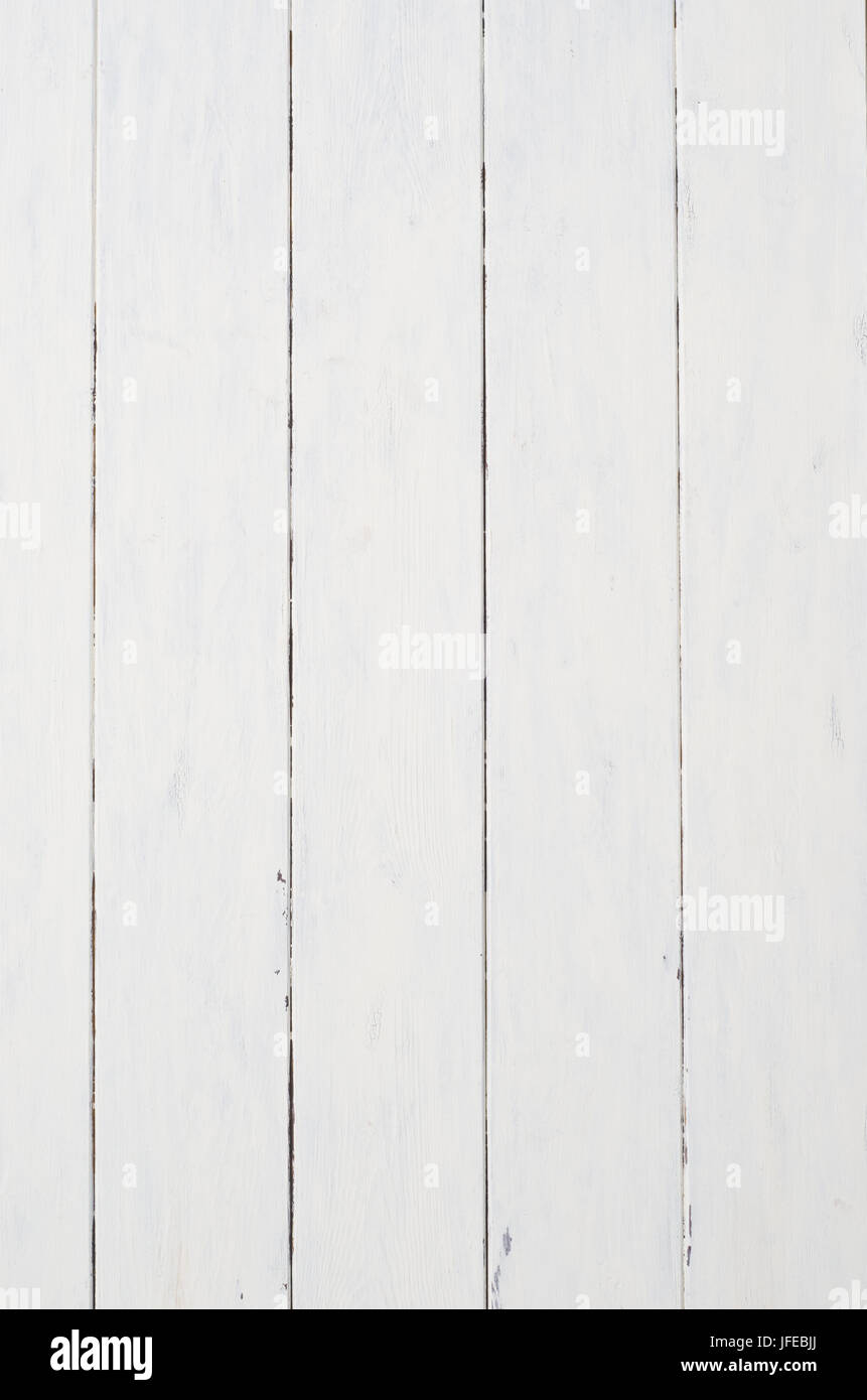 A badly painted patchy piece of old white wood planking that appears dilapidated, chipped, marked and worn. - Stock Image