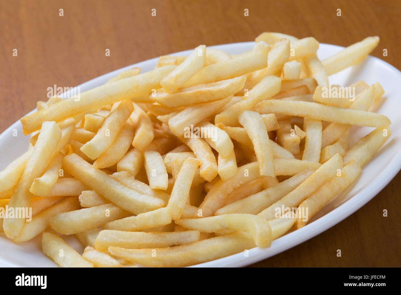 A plate full of delicious shoestring style french fries - Stock Image