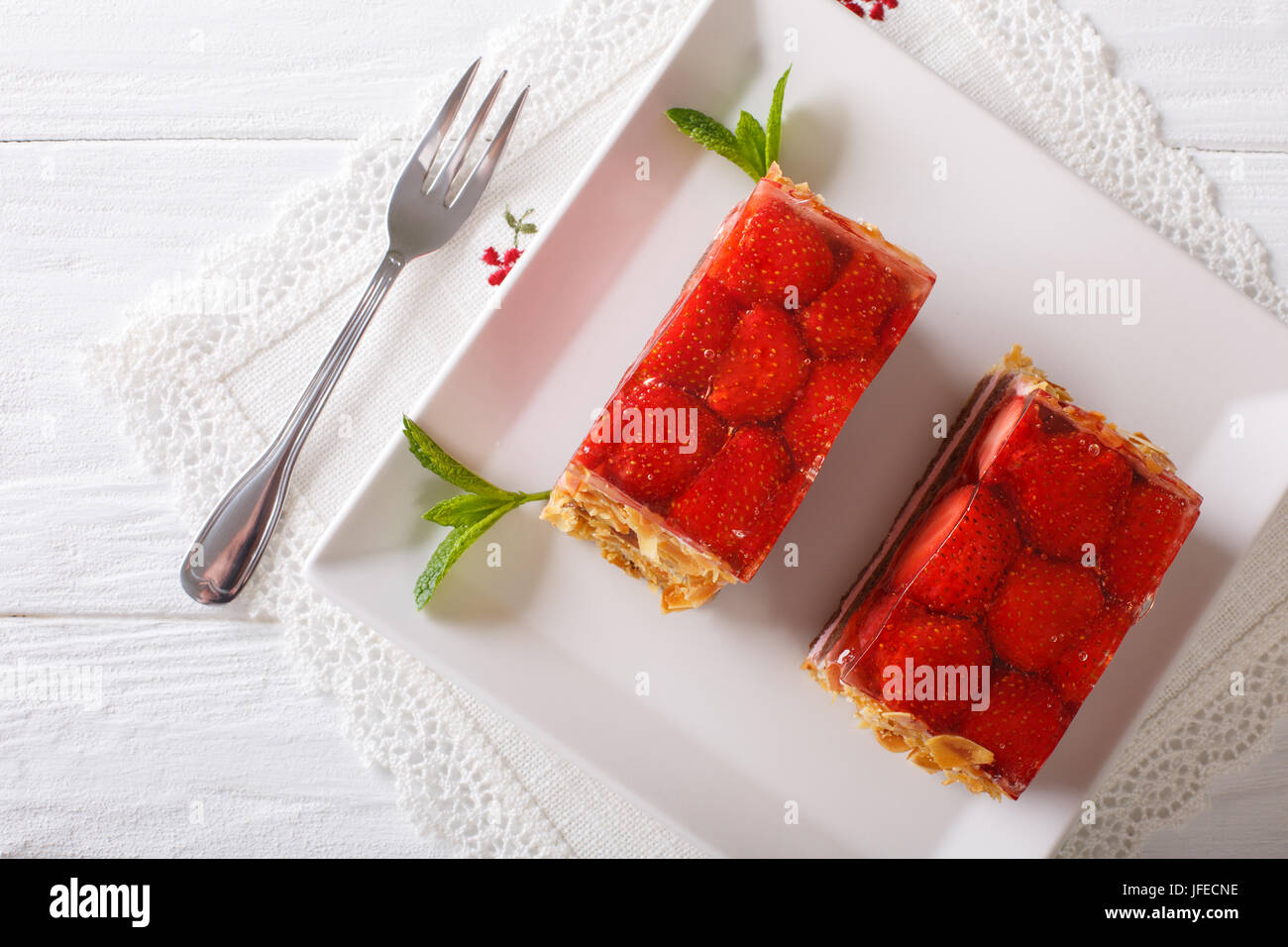 Strawberry jelly cake with almonds closeup on a plate. horizontal view from above - Stock Image