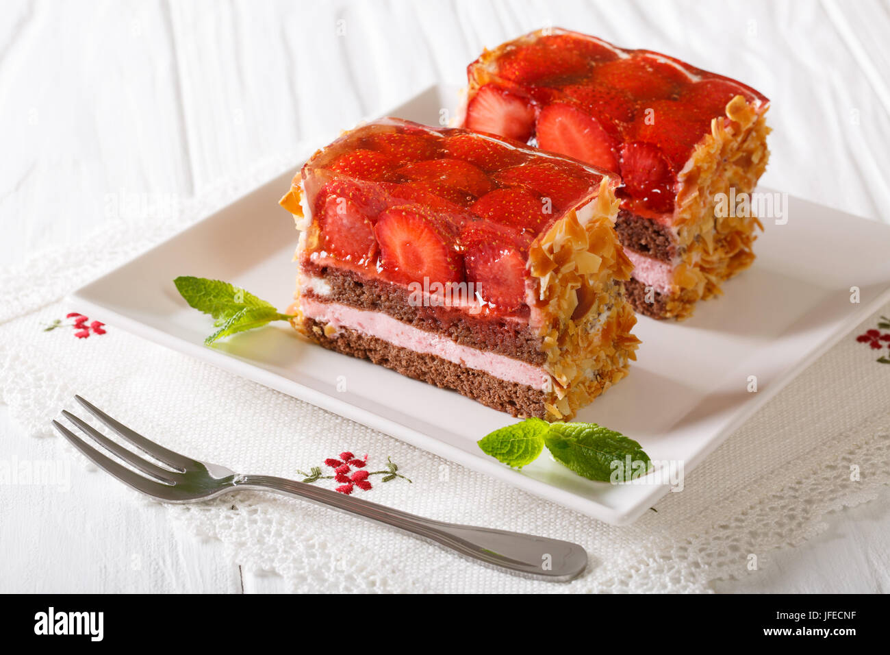Beautiful strawberry jelly cake with almonds close-up on a plate. horizontal - Stock Image