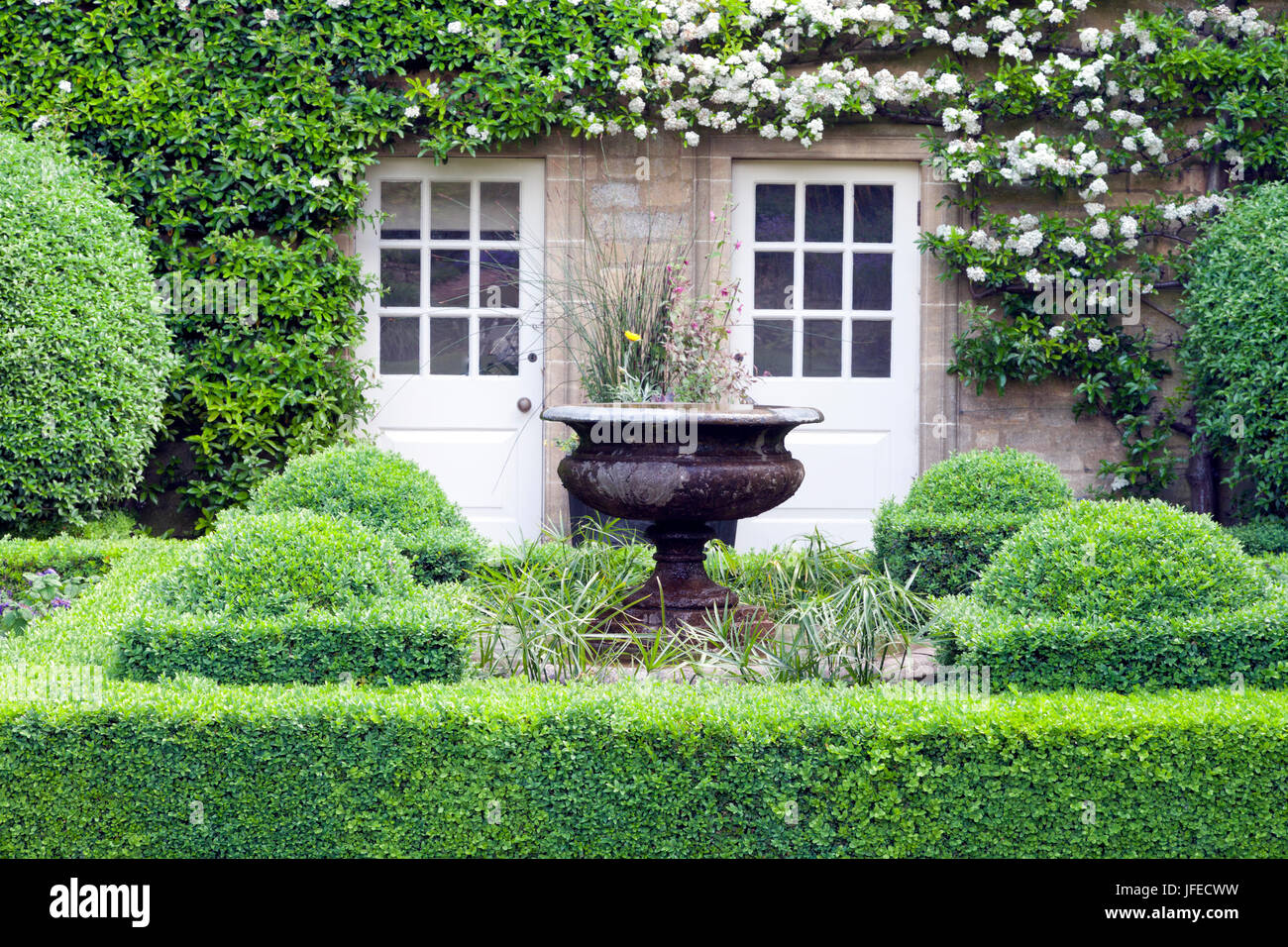 Flower Vase In Green Topiary Garden In Front Of A Stone English Stock Photo Alamy