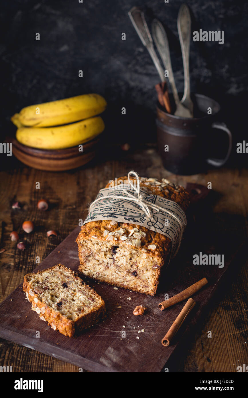 Banana bread with walnuts, cinnamon and chocolate chips on wooden cutting board. Selective focus. Food still life, Stock Photo