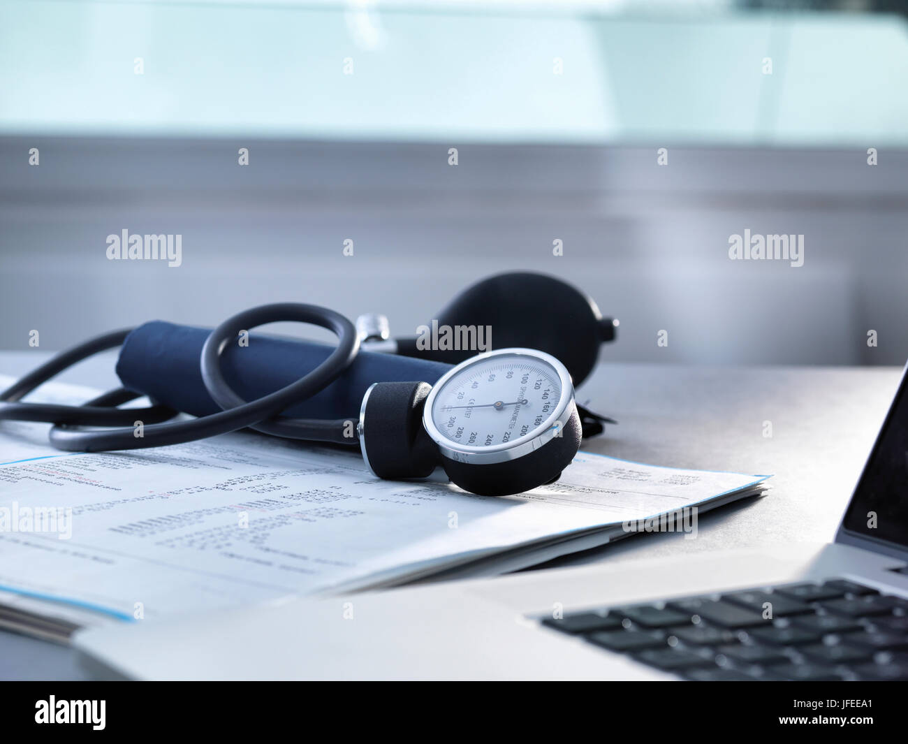 Blood pressure gauge sitting on a doctors desk. - Stock Image