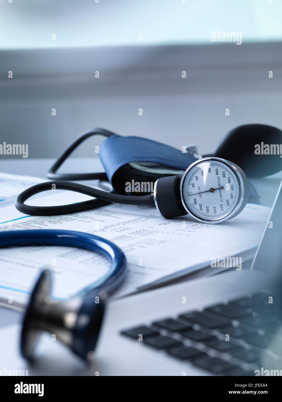 Blood pressure gauge and stethoscope sitting on a doctors desk. - Stock Image