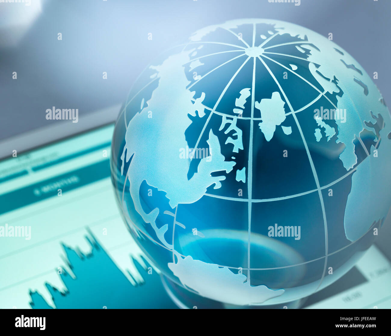 Global investments, conceptual image. Glass globe sitting on a digital table showing an increase in stock price. - Stock Image