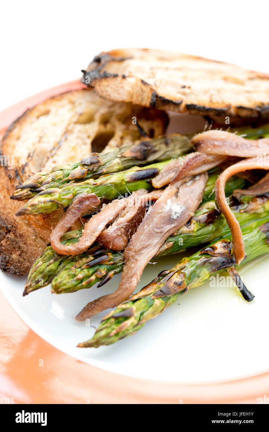 Asparagus, grilled, anchovies, bread, - Stock Image