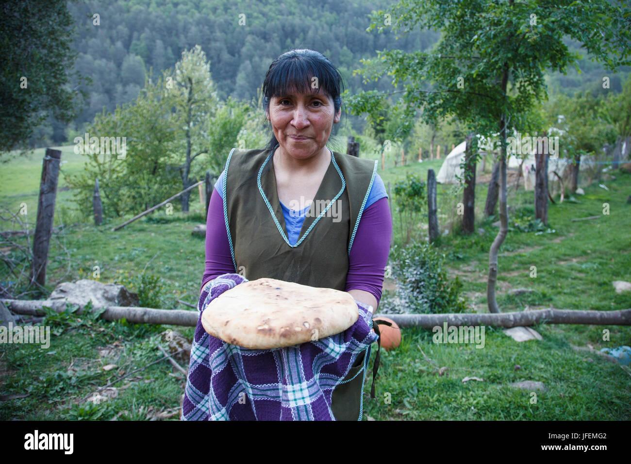 Chile, Araucania, Alto bio bio, Mapuche, woman, home-baked bread present, - Stock Image