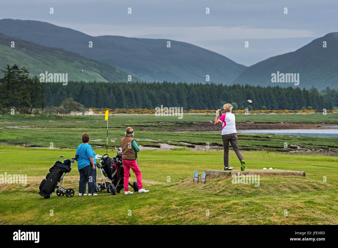 Three elderly women on Scottish golf course playing golf in Lochcarron, Wester Ross, Scotland, UK - Stock Image