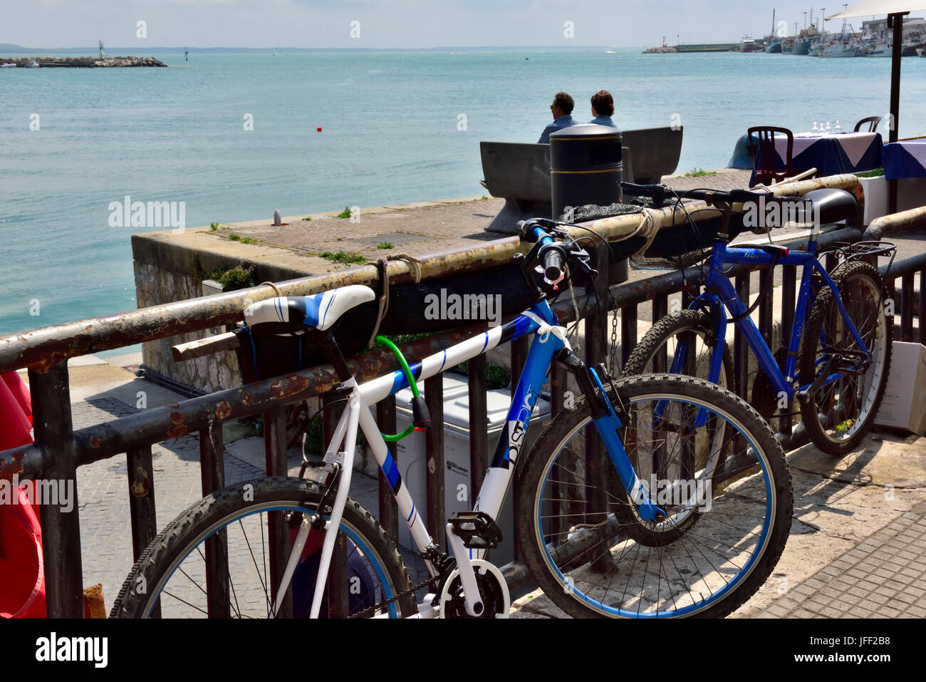 Two bicycles parked against railings, in background two people on bench looking out to sea - Stock Image