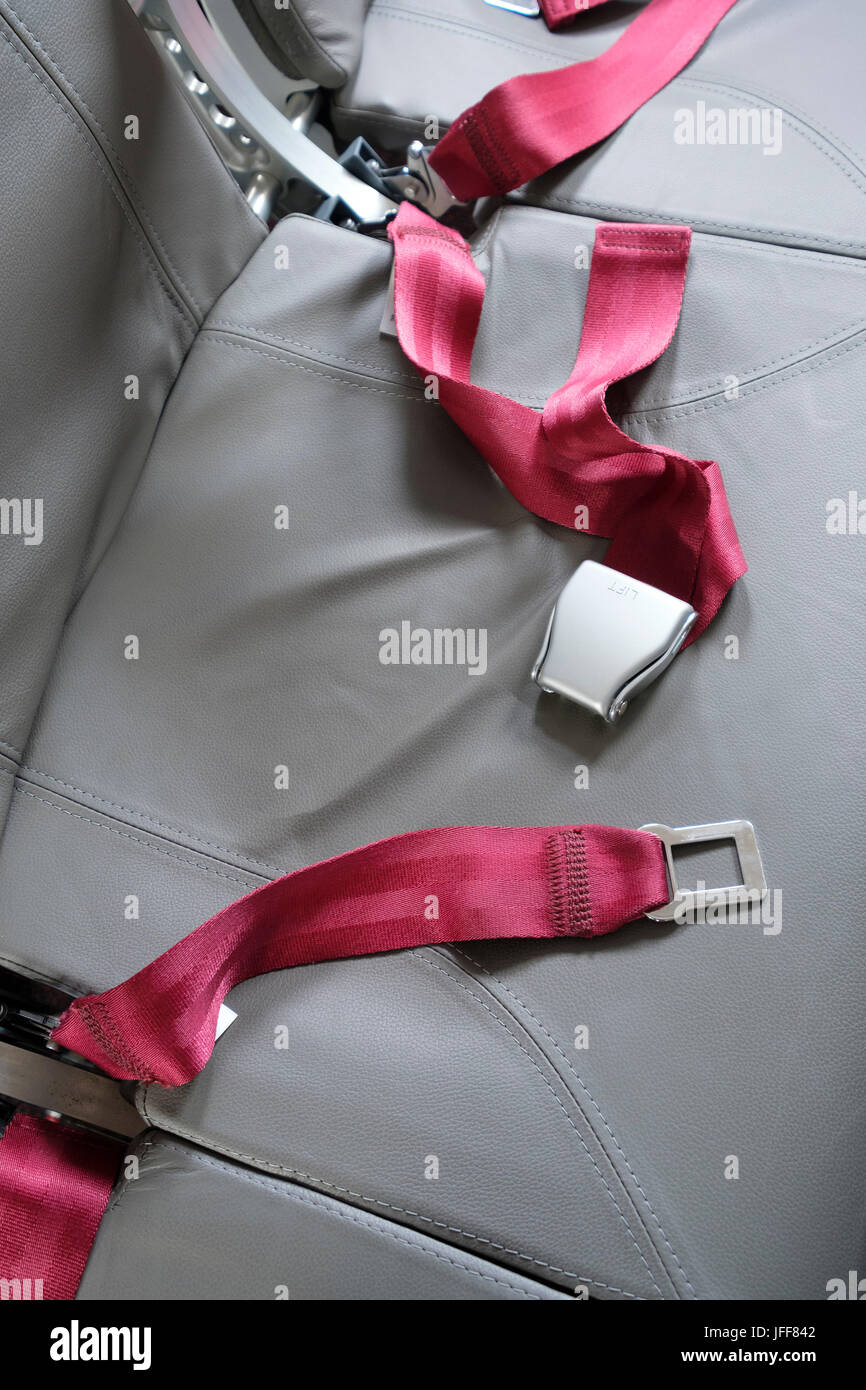 Unfastened seat belts on an airplane seat - Stock Image