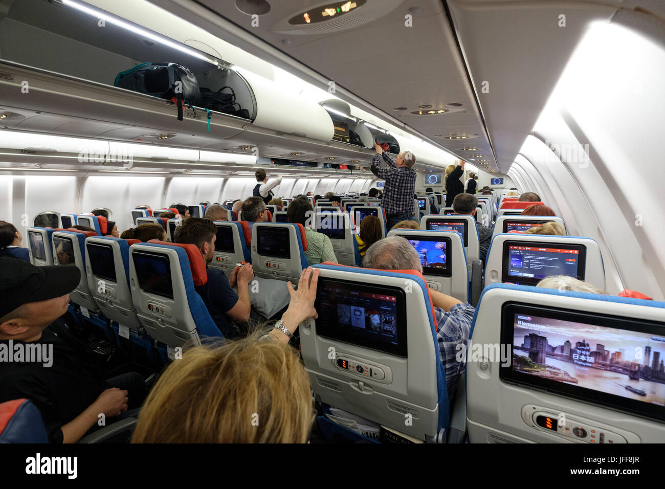 Passenger using an airplane's entertainment system - Stock Image