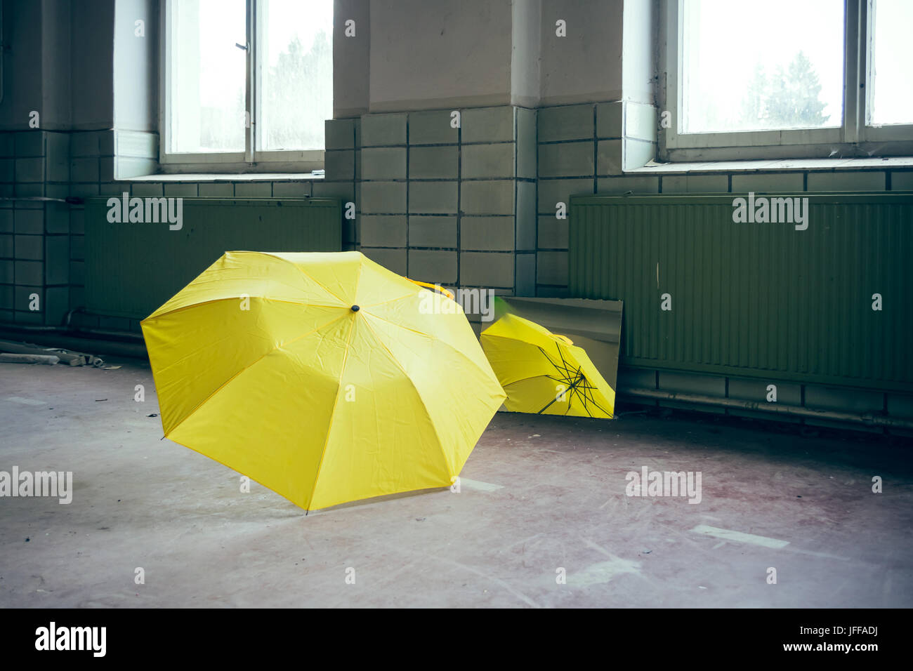 yellow umbrella in front of a mirror - Stock Image
