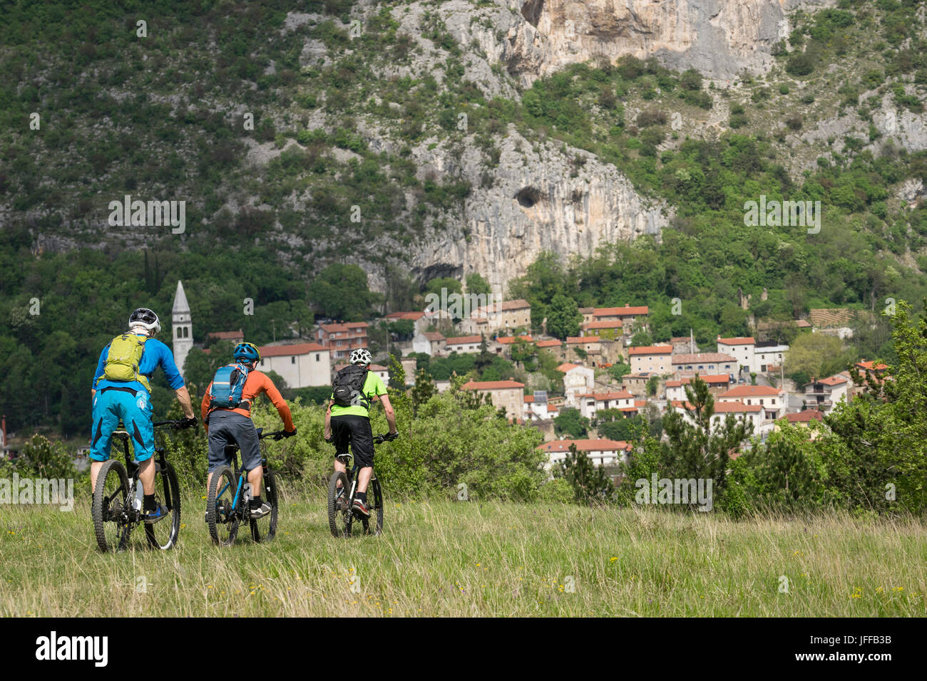 Mountain Biker riding cycle and overlooking houses by rocky mountain - Stock Image