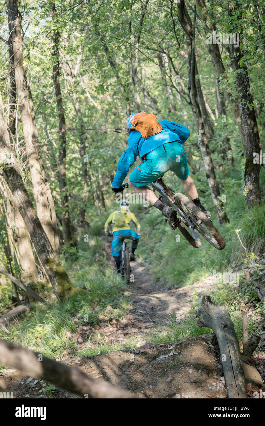 Biker jumping in mid-air while riding bike and following other biker on dirt path Stock Photo