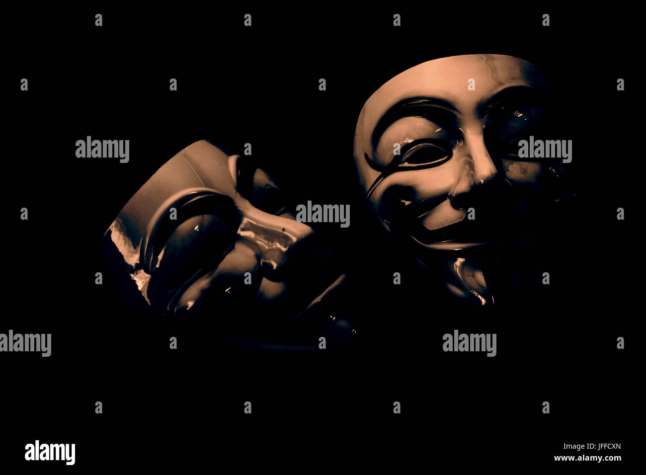 white and yellow anonymous masks on wood background - retro style - Stock Image
