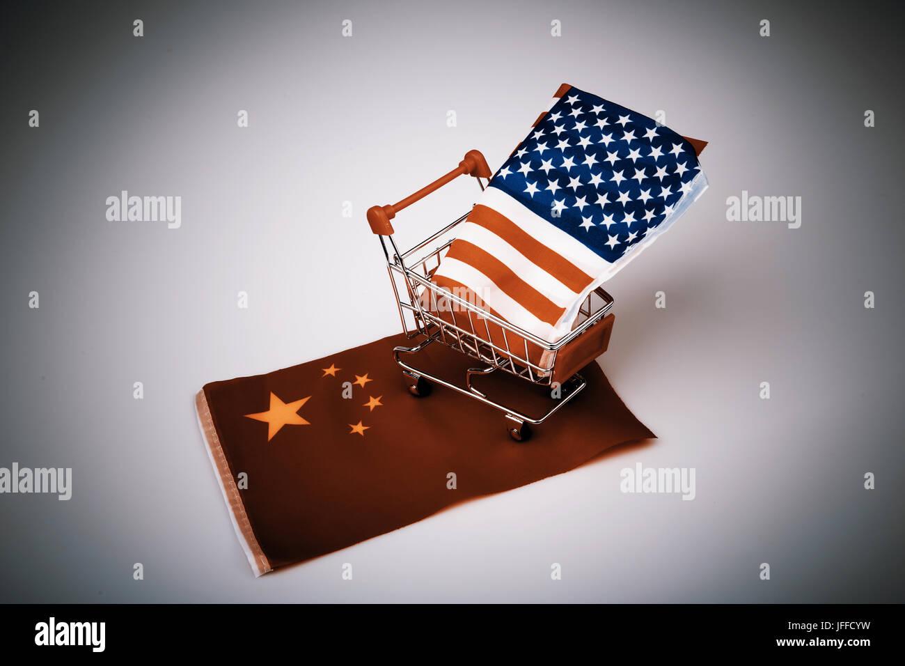 ping shopping cart with USA flag on China flag - China bought United states - Stock Image