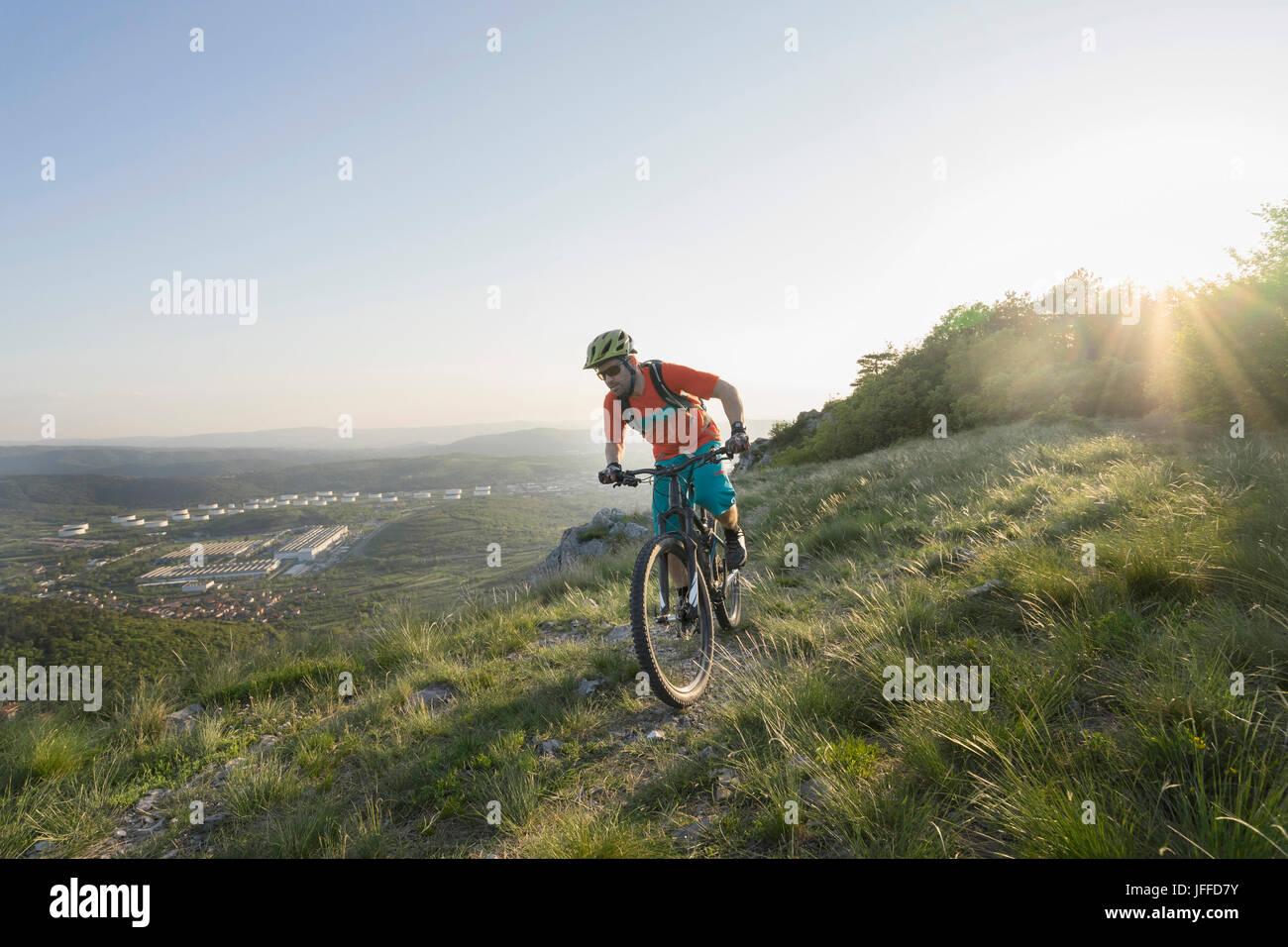Mature man riding mountain bike on hill - Stock Image