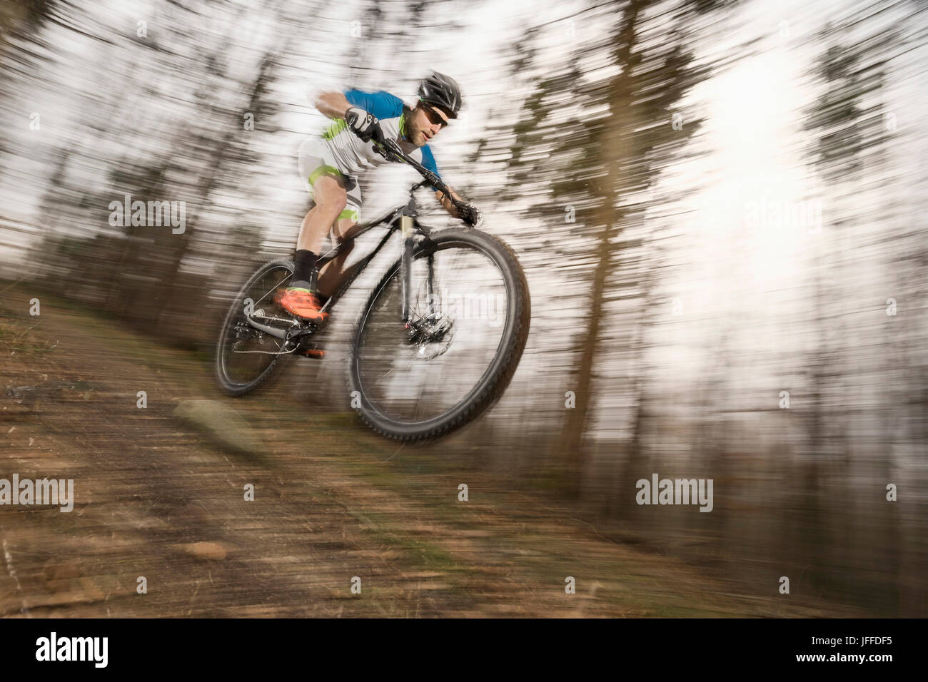Mountain biker performing stunt in forest - Stock Image