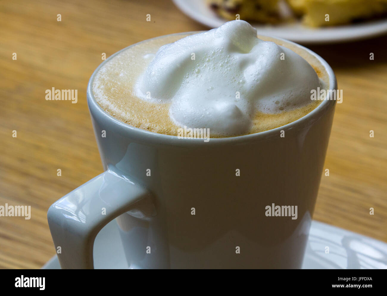 A large frothy topped hot cappuccino coffee in a plain porcelain cup. Stock Photo