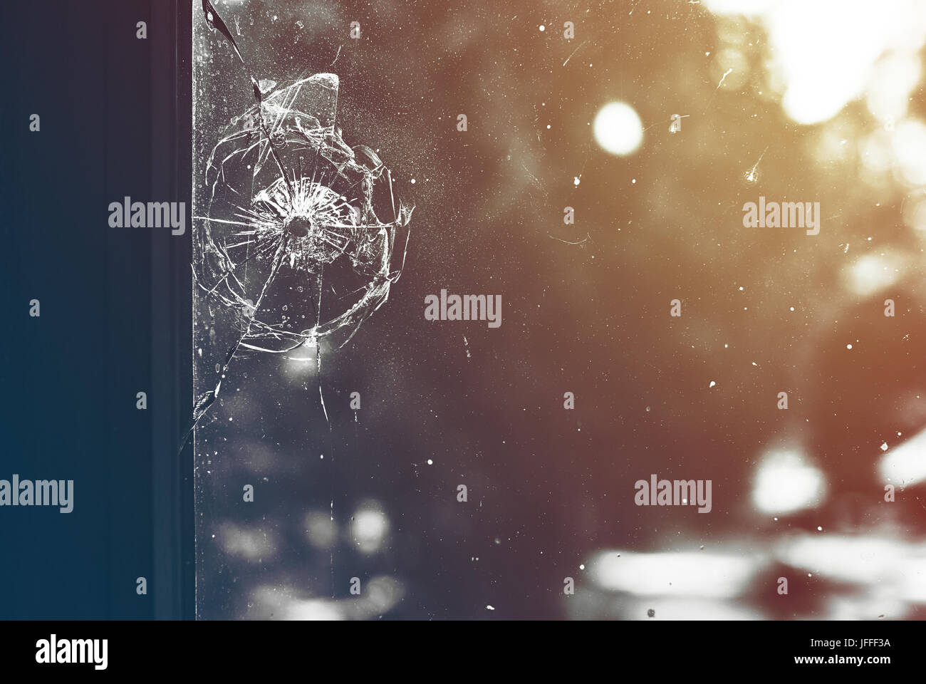 Bullet hole in the dirty window glass - Stock Image