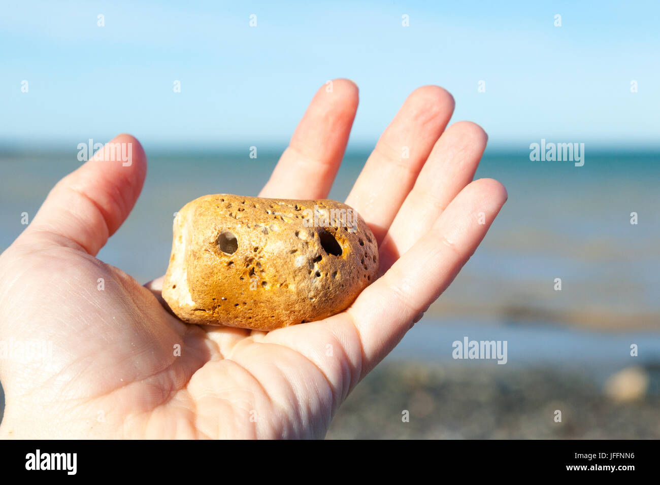 A cute 'pet rock' held in a hand - Stock Image