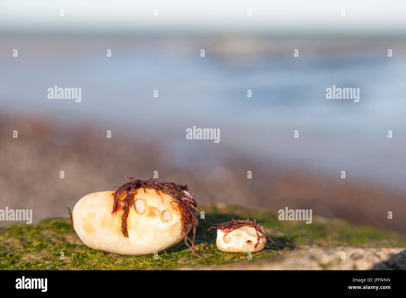 Rocks with humanlike faces that look like an adult with a child on beach - Stock Image
