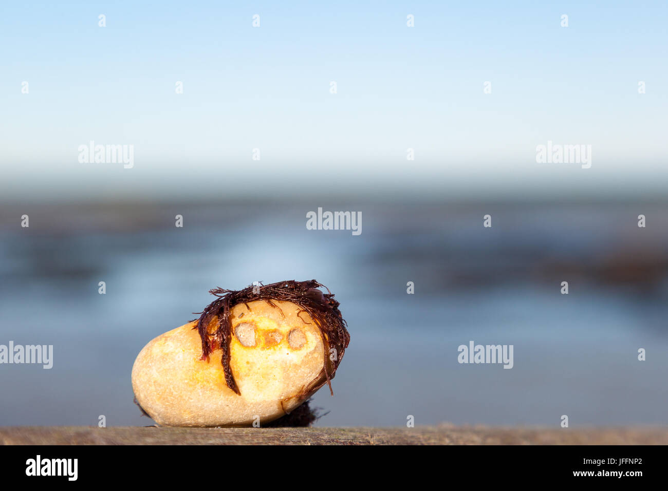 Rock with a humanlike face on beach - Stock Image